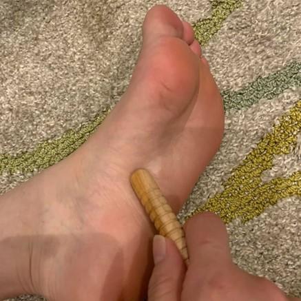 左足の土踏まずを指圧棒で刺激する画像