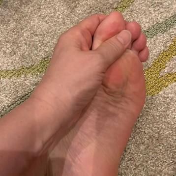 左足の親指を手で刺激する画像