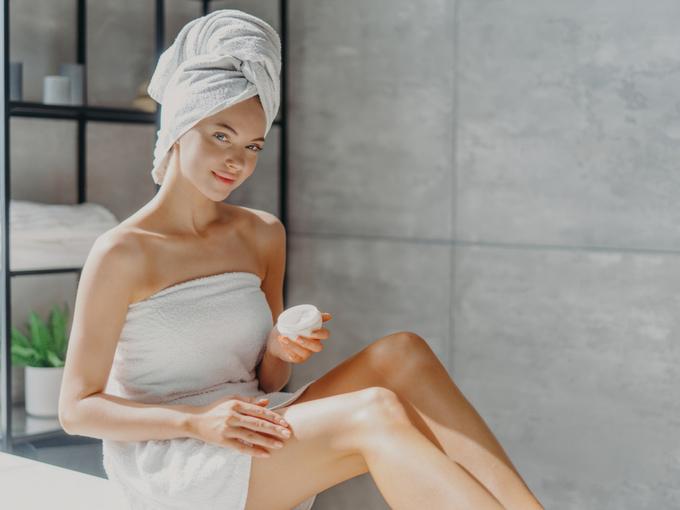 クリームを体に塗るお風呂上がりの女性
