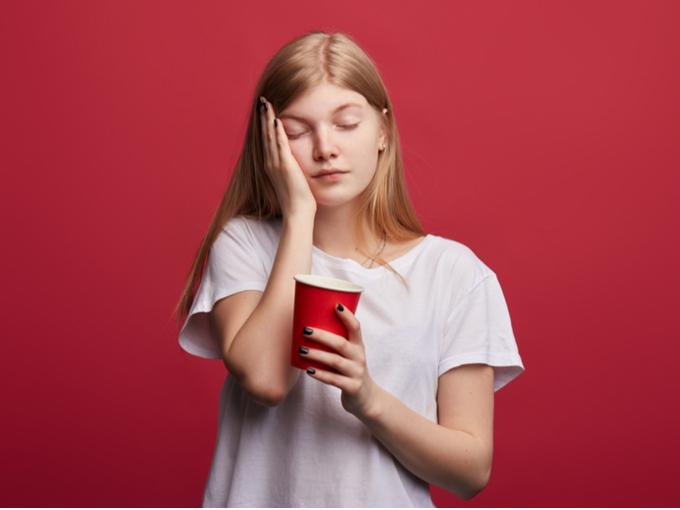 コーヒーを片手に顔に手を当てる女性