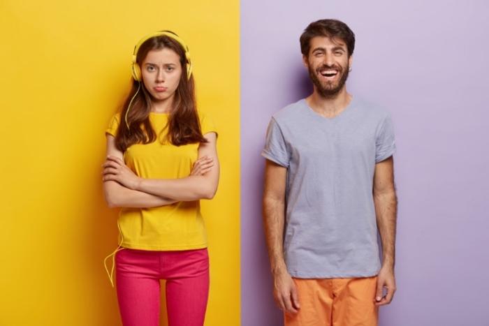 不満げな女性と笑顔の男性画像