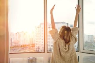朝日に向って手を挙げる女性