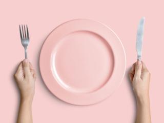 ピンクのお皿とカトラリーを持つ女性の手元