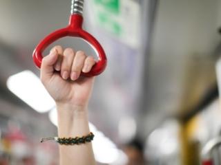 電車のつり革をつかむ女性の手