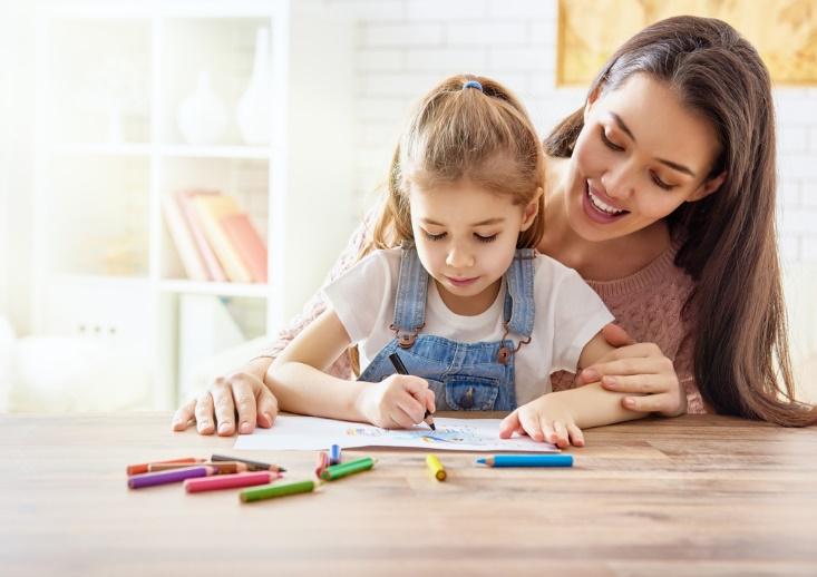絵を描いている子を見守る母親画像