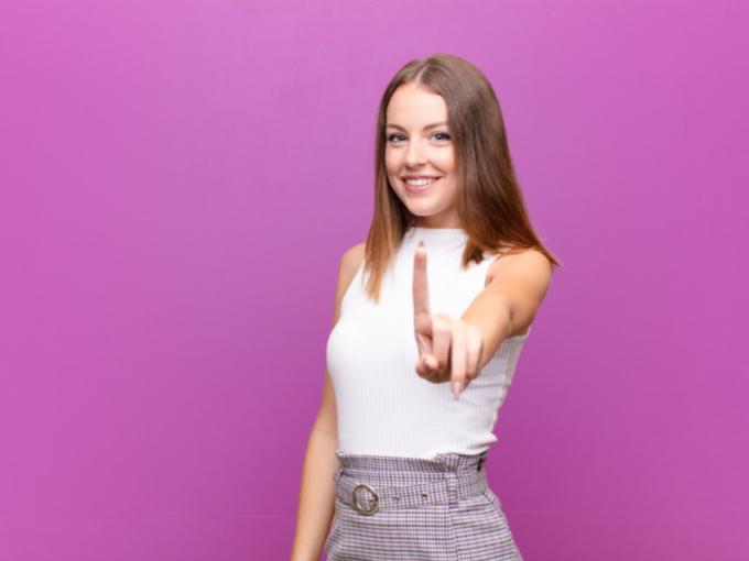 指を突き出す笑顔の女性
