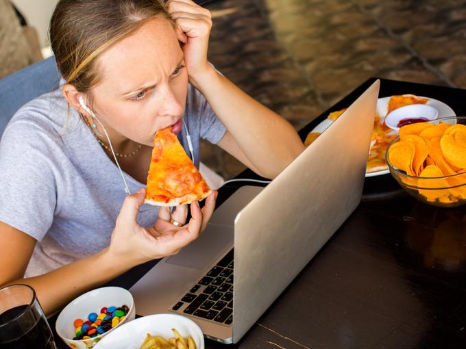 ピザを食べながらパソコンの画面を見る女性
