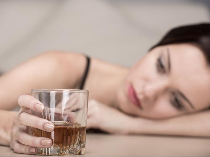 アルコールの入ったグラスを手にする女性