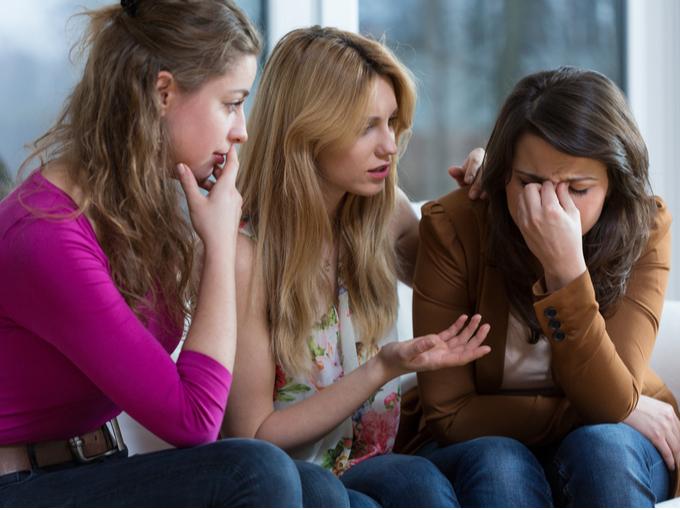 落ち込む女性を慰める友人たち