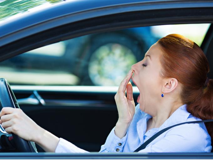 車の運転中にあくびをする女性