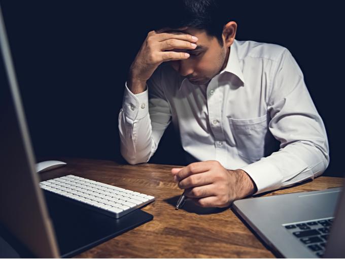 パソコンの前で疲れた様子の男性