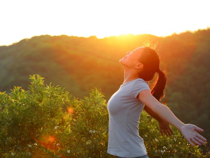 自然のなかで深呼吸する女性