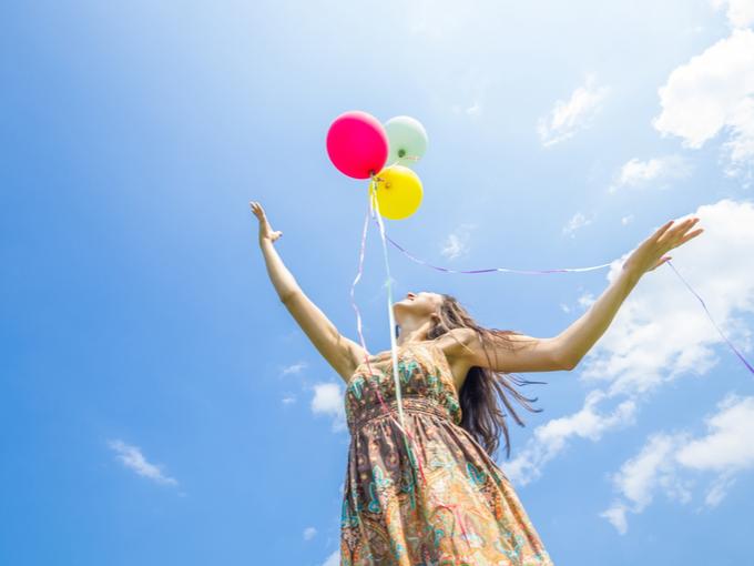 空に風船を手放す女性