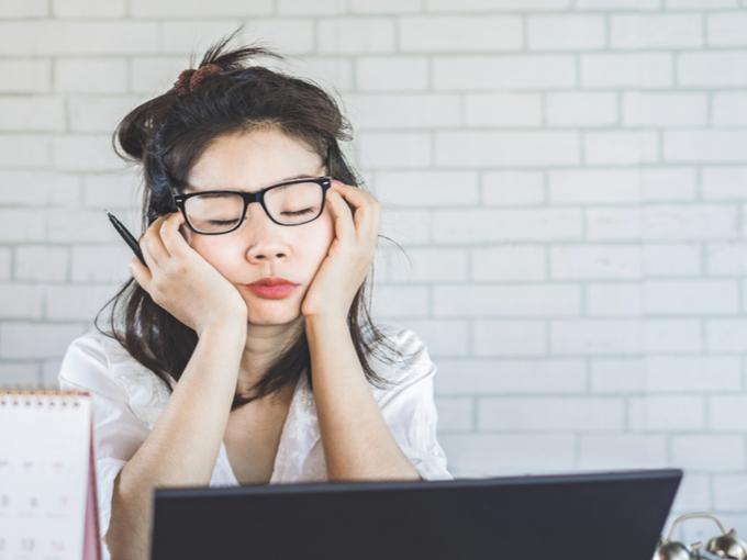 パソコンを前にうたたねする女性