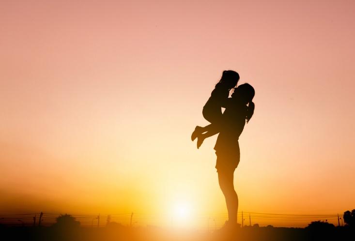 夕陽をバックにして子どもを抱き上げる母親画像