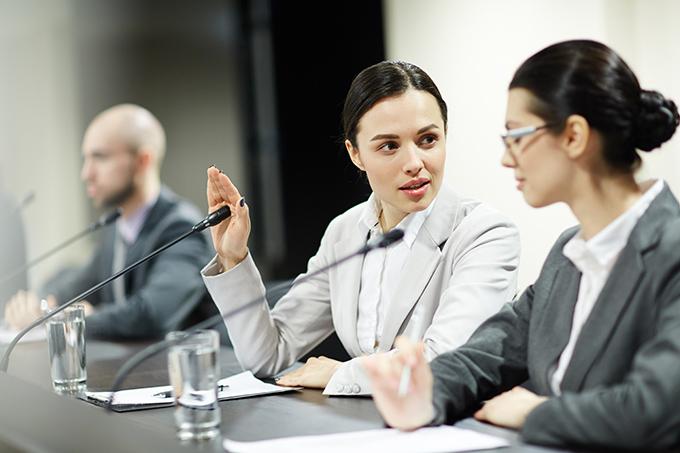 会議で挙手する女性