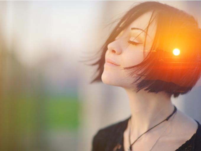 目をつぶって瞑想する女性