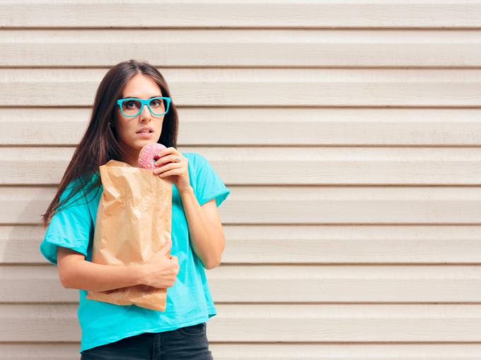 買い物帰りの途中でドーナツを食べようとする女性