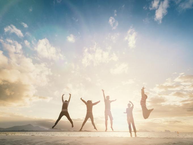 浜辺で朝日を浴びながらジャンプする人たちのシルエット