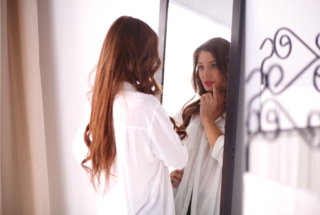 等身大の鏡をみているロングヘアの女性
