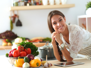 キッチンで野菜などを前にポーズをとる女性