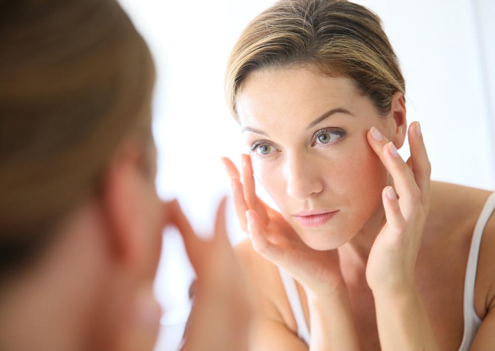 顔を鏡でじっくり見ている女性