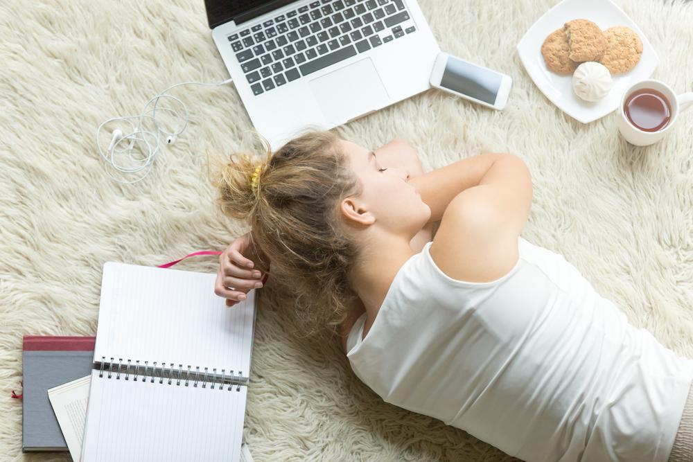 パソコンやノートを広げて横になっている女性