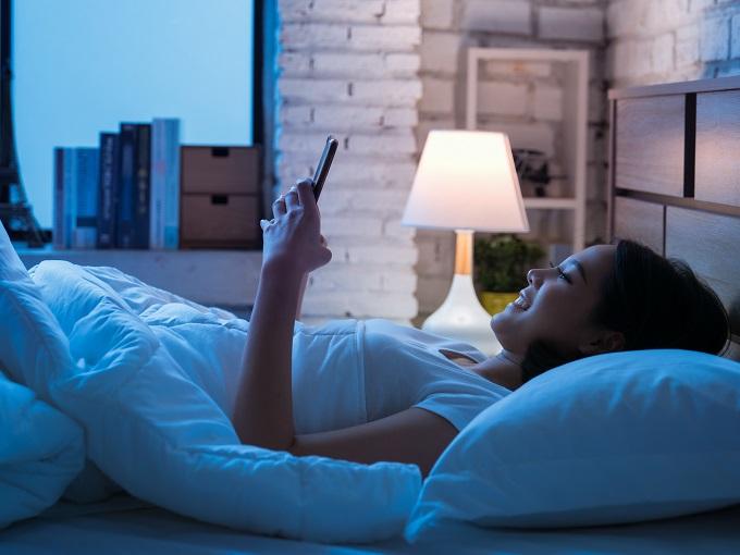 ベッドでスマホを見ている女性の画像