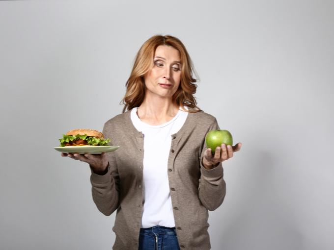 ハンバーガーとりんごを手にする女性