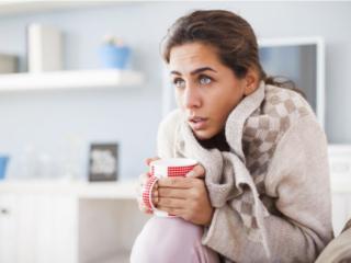 温かい飲み物を持って体を温める女性