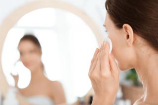 ほおのパフを当てて鏡を見ている女性