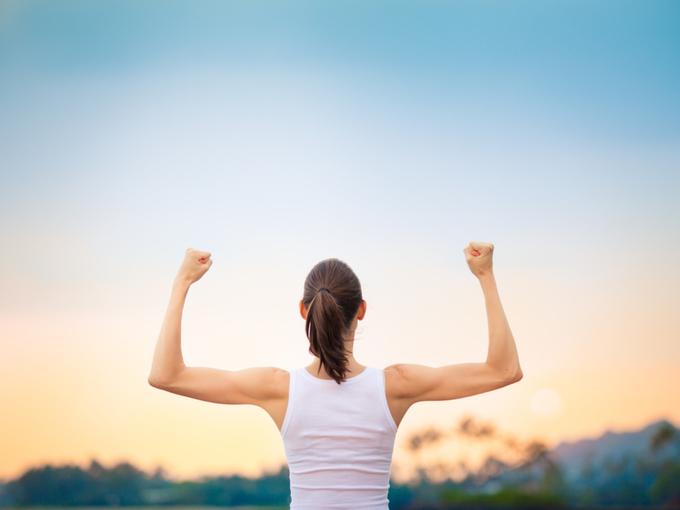 腕の筋肉に力を入れて両手を上げる女性