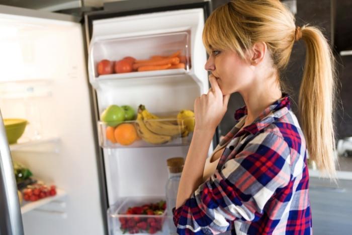 冷蔵庫の前で迷う女性の画像