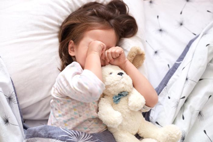 ベッドで寝ながら目を擦っている子ども