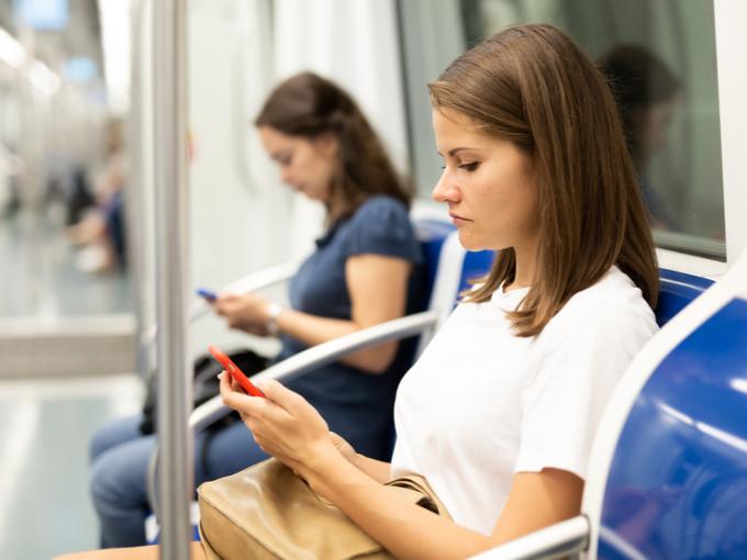 電車内でSNSを見る女性