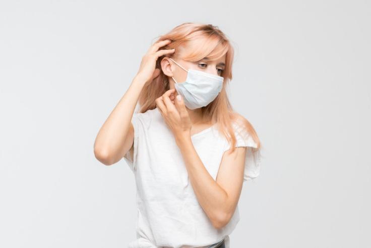 髪の毛をかき上げるマスクをした女性