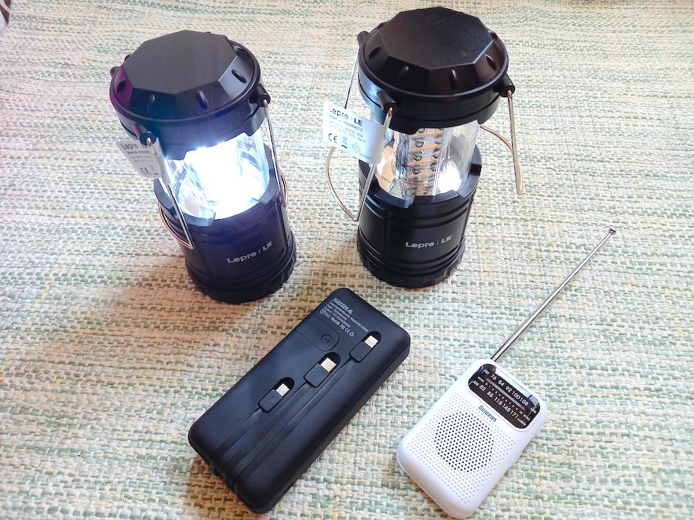 電気のついたLEDランタンと携帯ラジオ、モバイルバッテリー