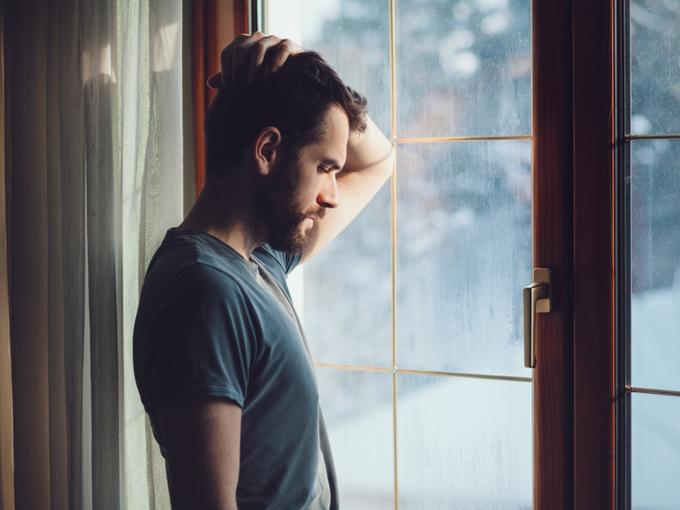 窓際で思い悩む男性
