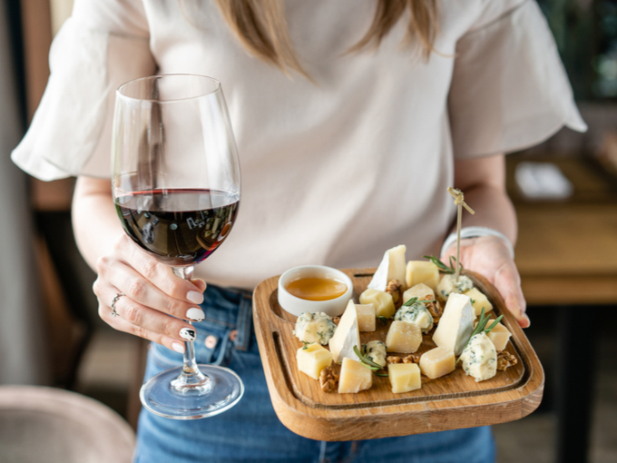 ワインとチーズを差し出す女性