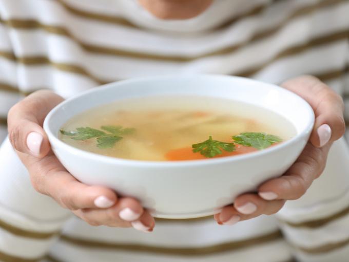 スープを手に持つ女性