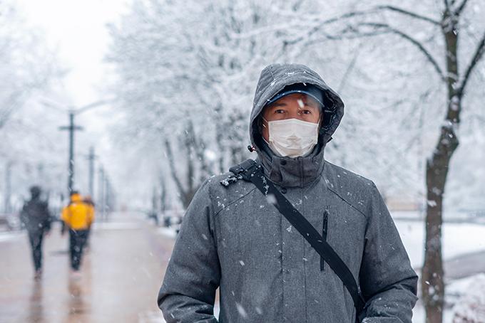 雪が降るなか、外出する男性