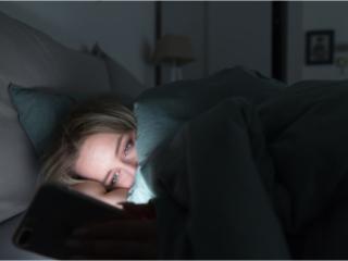 寝ながらスマホを見る女性