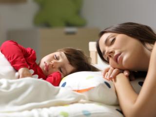 子どもと一緒に眠る母親