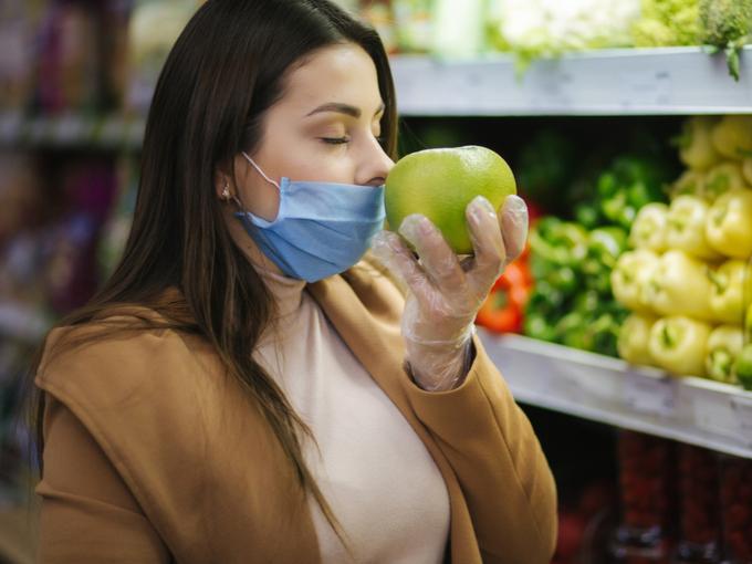 フルーツの香りをかぐマスクの女性