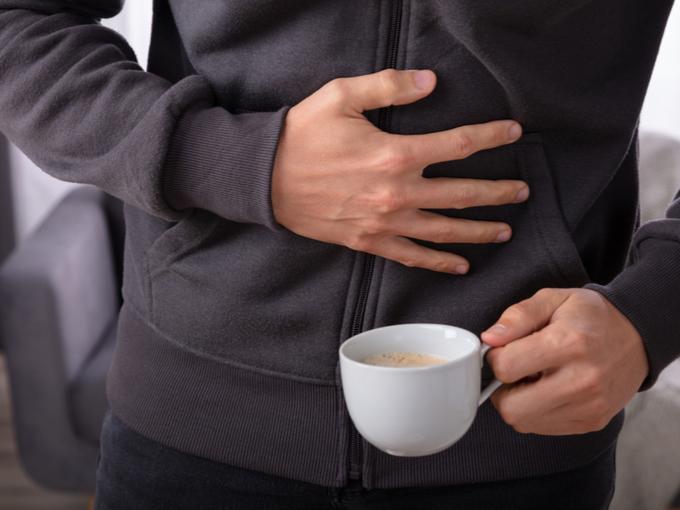胃腸付近を押さえる男性