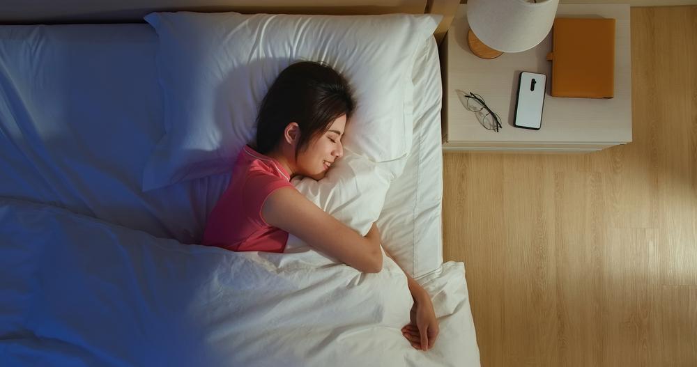 ベッドで枕を抱えながら横向きで寝ている女性