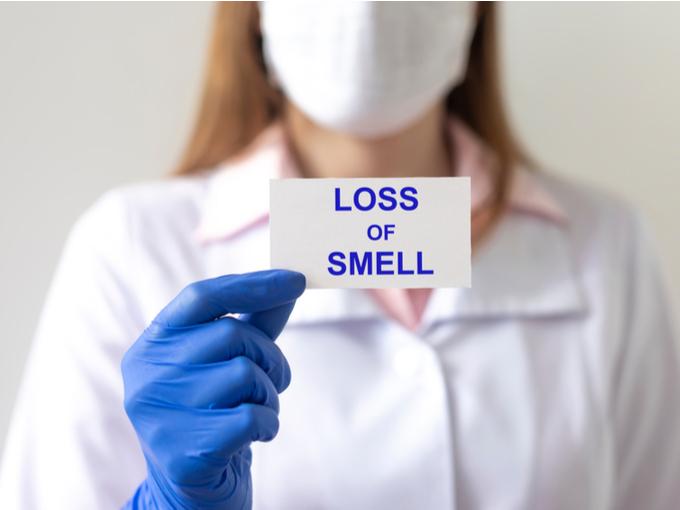 嗅覚を失ったことも示すカードを持つ女性