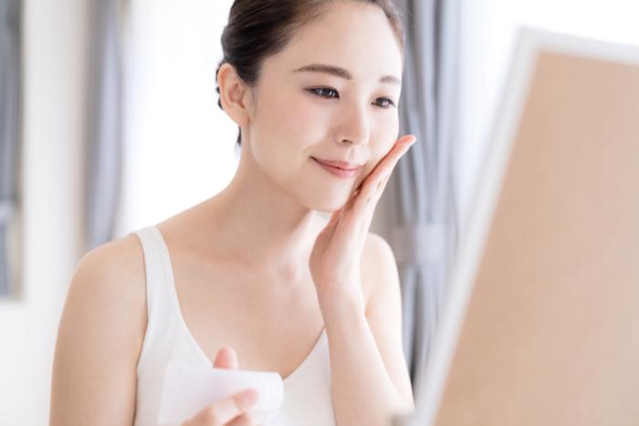 鏡を見てスキンケアしている女性