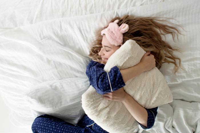 枕を抱き抱えて笑顔で寝ている女性