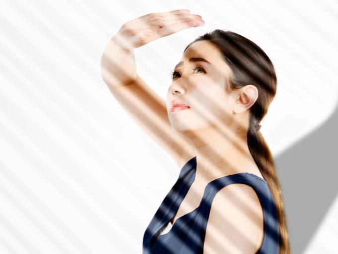 日差しを手で遮る女性